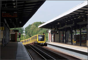 Abstieg nach dem Halt in Wuhletal -     Ein Kleinprofil-U-Bahnzug der Baureihe IK auf der Großprofil-Linie U5 verlässt in Richtung Alexanderplatz  den U- und S-Bahnhof Wuhletal im