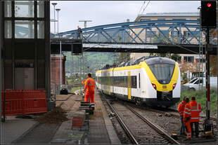 Die Farben stehen im gut -    Ein weiß-gelb-schwarzer Triebzug der Baureihe 440 zwischen orangen Männern bei der Abfahrt im Hauptbahnhof von Freiburg,    07.10.2019 (M)
