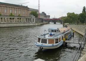 Ein Regionalexpress fährt über die Spree und davor wartert ein Tour-Schiff auf seine Passagiere.