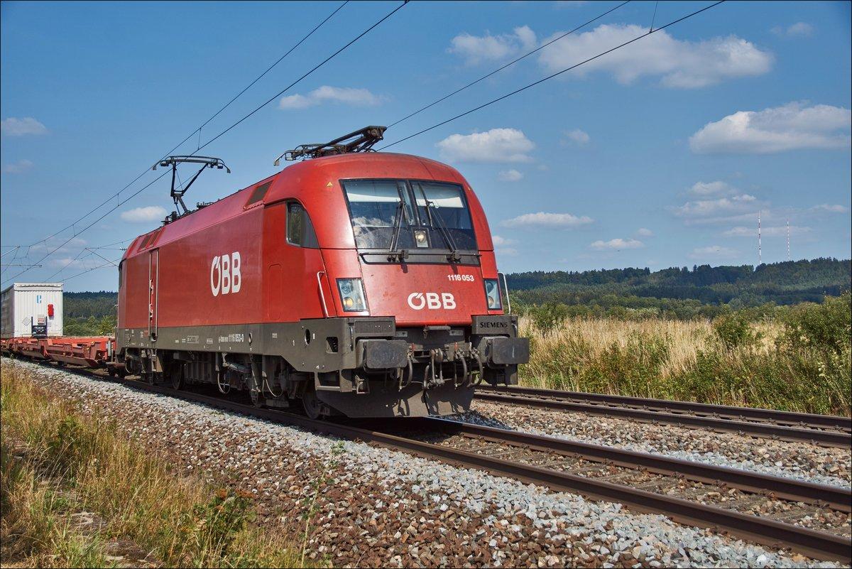 1116 053 zu sehen mit einen Aufliegerzug bei Pölling am 16.08.2018.