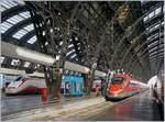In Milano Centrale warten ein FS Trenitalia ETR 400  Frecciarossa 1000  und durch die mächtige Konstruktion der Bahnhofshalle etwas verdeckt ein  Freccia Bianca  auf die Abfahrt.